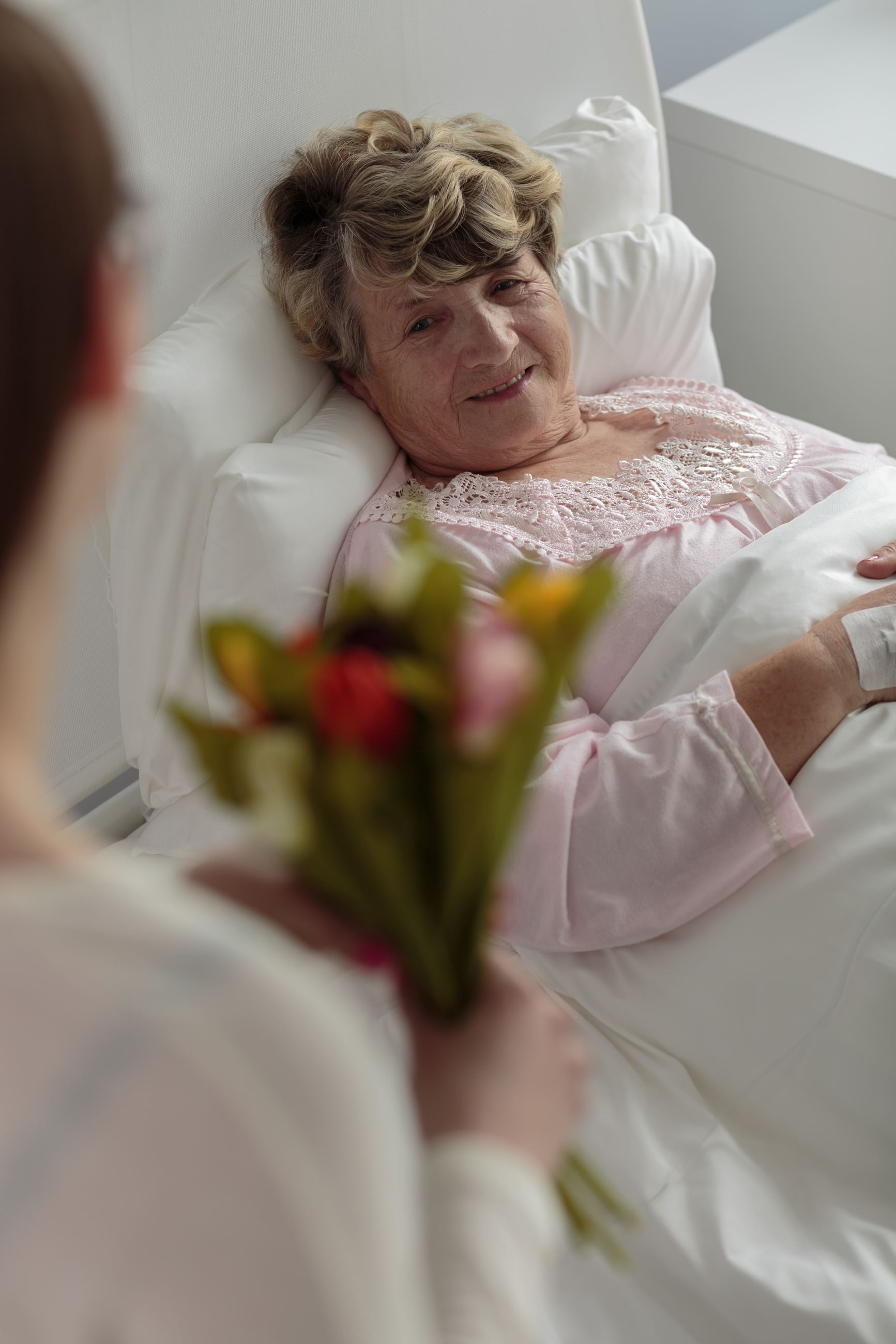 Girl visiting grandmother in the hopsital with tulips