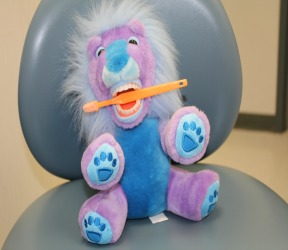 Purple stuff animal with a toothbrush
